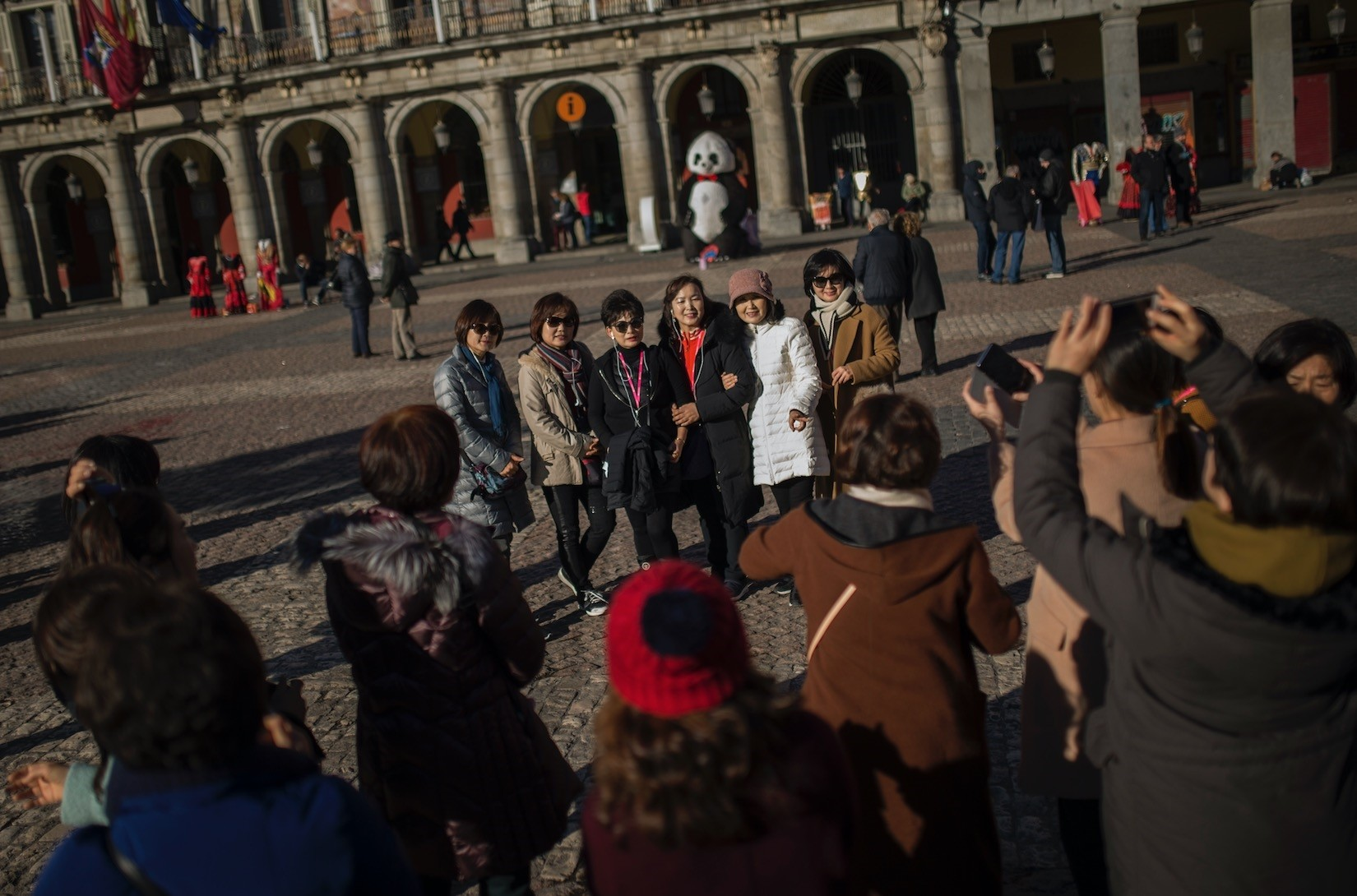 Tourists pose for a photograph at Mayor square in central Madrid. Spain says it has broken its record of international visitors for the fifth consecutive year in 2017 with 82 mn tourists that chose restive Catalonia as their main Spanish destination.