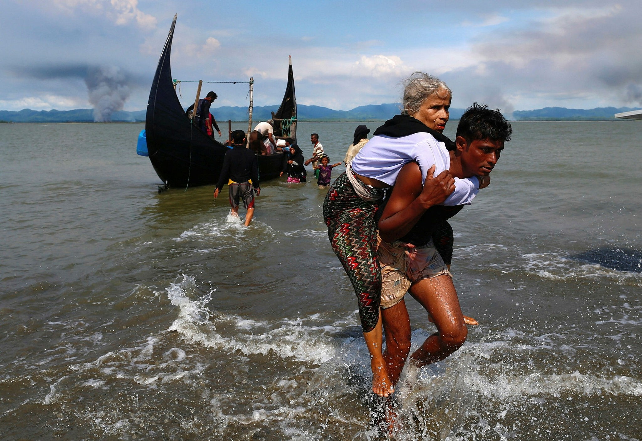 Smoke rises on Myanmar's side of border as an old Rohingya refugee woman is carried after crossing the Bangladesh-Myanmar border by boat through the Bay of Bengal, Sept. 15.
