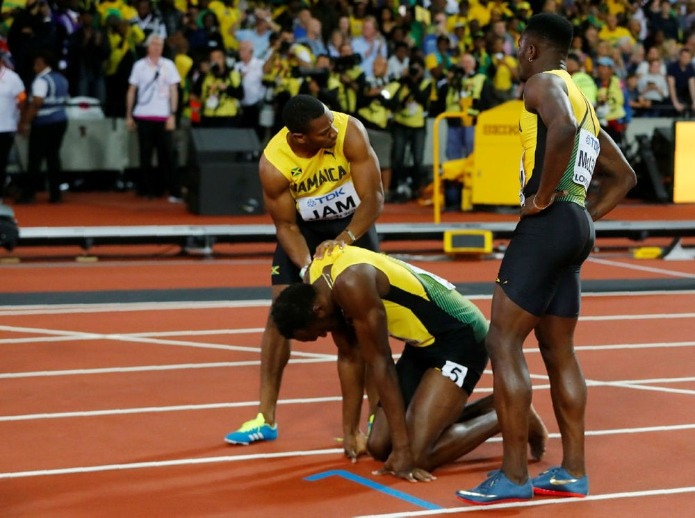 Usain Bolt of Jamaica reacts with Yohan Blake after sustaining an injury. (REUTERS Photo)