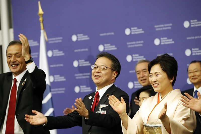 Japan's Economy, Trade and Industry Minister Hiroshige Seko, center, applauds at the164th General Assembly of the Bureau International des Expositions (BIE) in Paris, Friday, Nov. 23, 2018. (AP Photo)