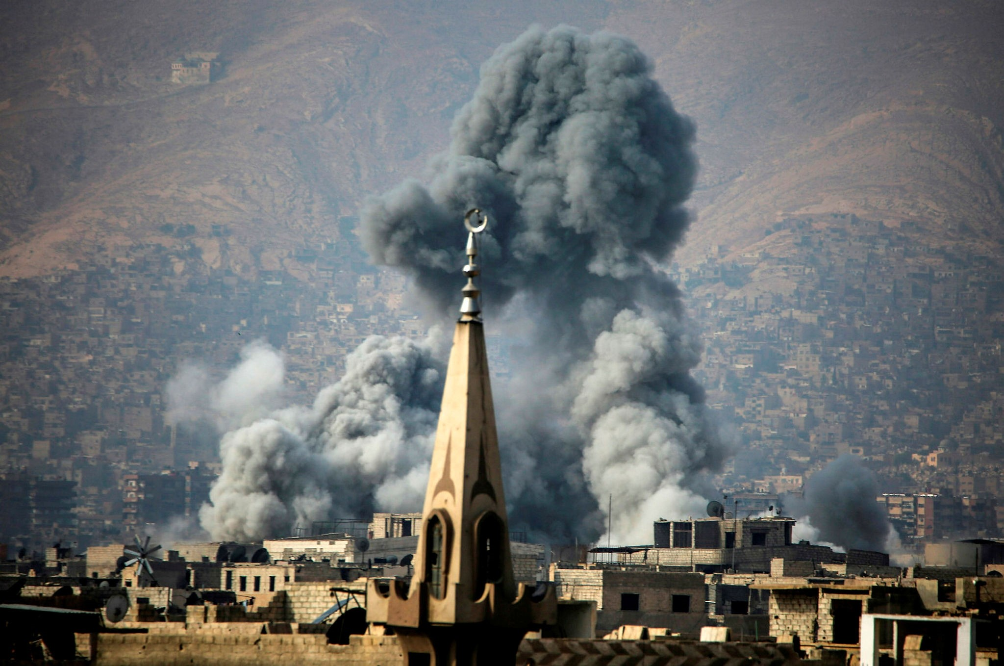A picture taken on November 23, 2017 shows smoke rising following a reported air strike on the moderate opposition-held besieged town of Arbin, in the Eastern Ghouta region on the outskirts of Damascus. (AFP Photo)
