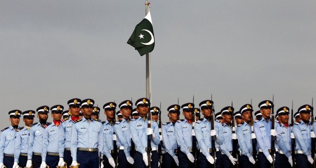 A Pakistan's national flag flies on mast as the members of the Pakistan Air Force march during Defence Day ceremonies, or Pakistan's Memorial Day, to express solidarity with the people of Kashmir, in Karachi, Sept. 6, 2019. Reuters Photo