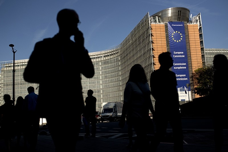 People walk past the European Commission headquarters in Brussels, Monday, Oct. 15, 2018. (AP Photo)