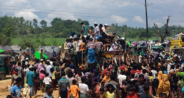Rohingya refugees climb a truck to receive aid distributed by local organisations at Balukhali makeshift refugee camp in Cox's Bazar, Bangladesh (Reuters Photo)