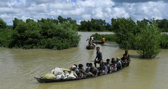Rohingya refugees arrive on a boat after crossing the Naf river from Myanmar into Bangladesh in Whaikhyang, Oct. 9.