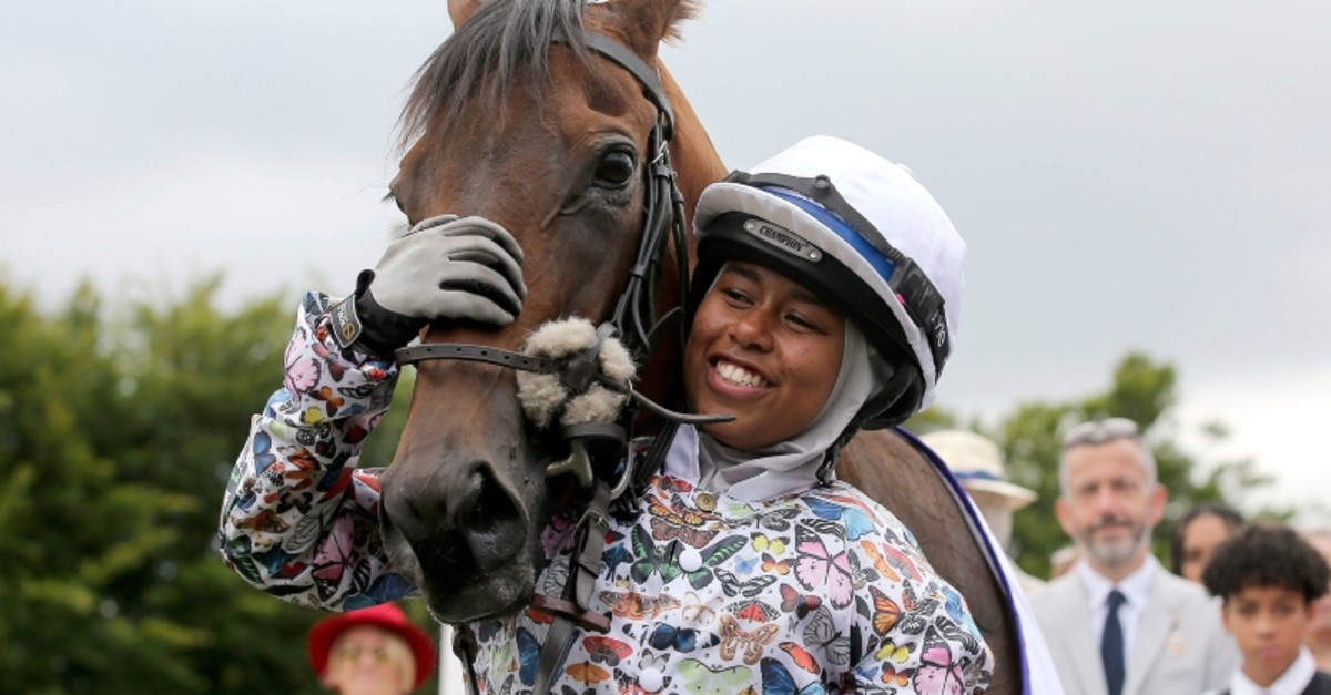 British Jockey Khadijah Mellah cuddles Haverland after winning the all-female Magnolia Cup - an amateur jockey's charity race, during day three of the Qatar Goodwood Festival at Goodwood Racecourse, in Chichester, England, Aug. 1, 2019. (AP Photo)