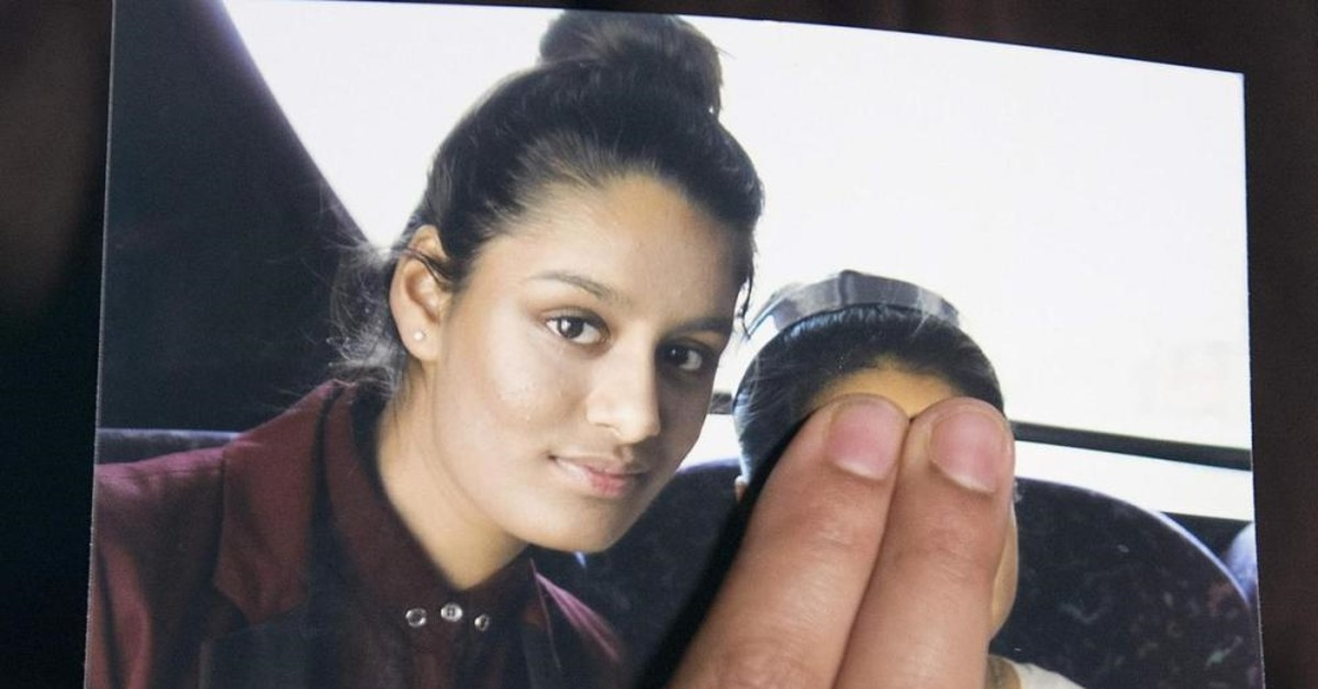 Renu Begum, eldest sister of missing 19-year-old UK girl Shamima Begum, holds a picture of her sister taken with another girl, whose face is covered in the photo to protect her identity, while being interviewed by the media in London, Feb. 22, 2015