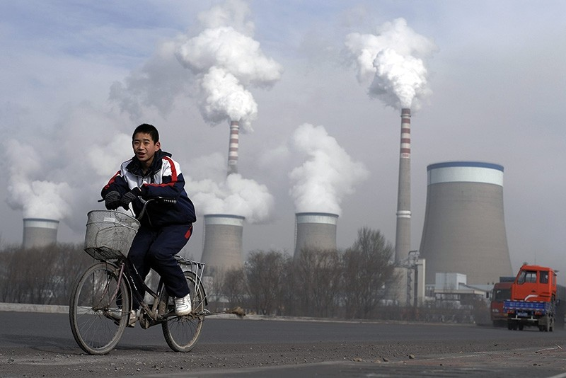 In this Dec. 3, 2009 file photo, a Chinese boy cycles past a cooling towers of a coal-fired power plant in Dadong, Shanxi province, China. (AP Photo)