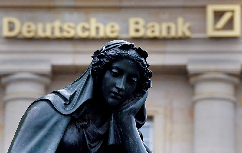 A statue is seen next to the logo of Germany's Deutsche Bank in Frankfurt, Germany, January 26, 2016. (Reuters Photo)