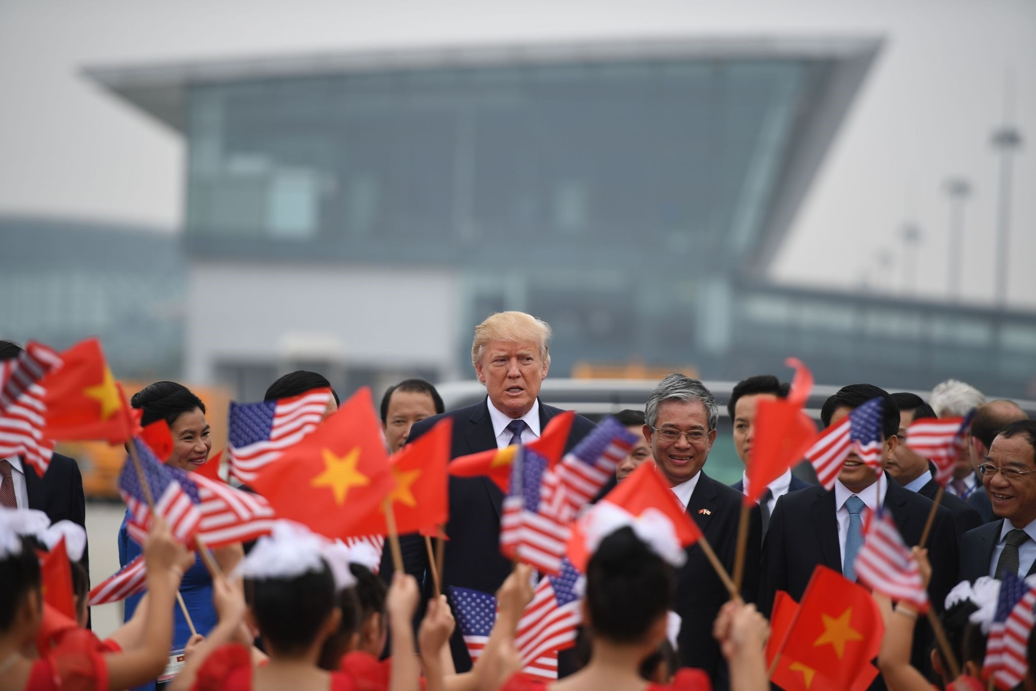 President Donald Trump watches as young girls wave U.S. and Vietnamese national flags before boarding Air Force One to depart to the Philippines, at the airport in Hanoi, Vietnam, Nov. 12.