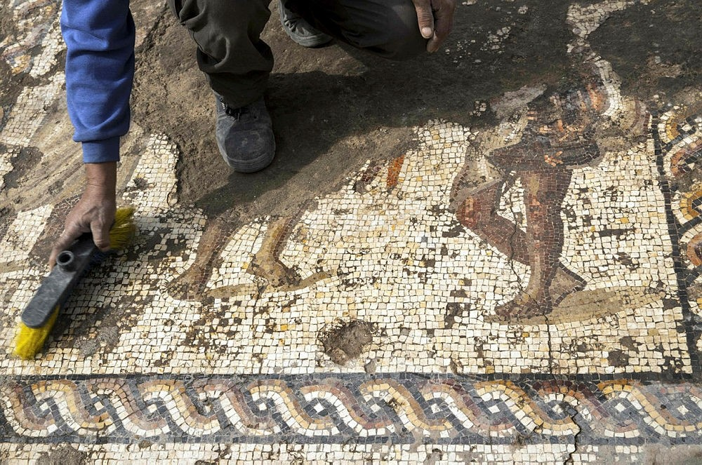 A worker from the Israeli Antiquity Authority (IAA) cleans a rare Roman mosaic from the 2ndu20133rd centuries at the Israeli Caesarea National Park on February 8, 2018. (AFP Photo)