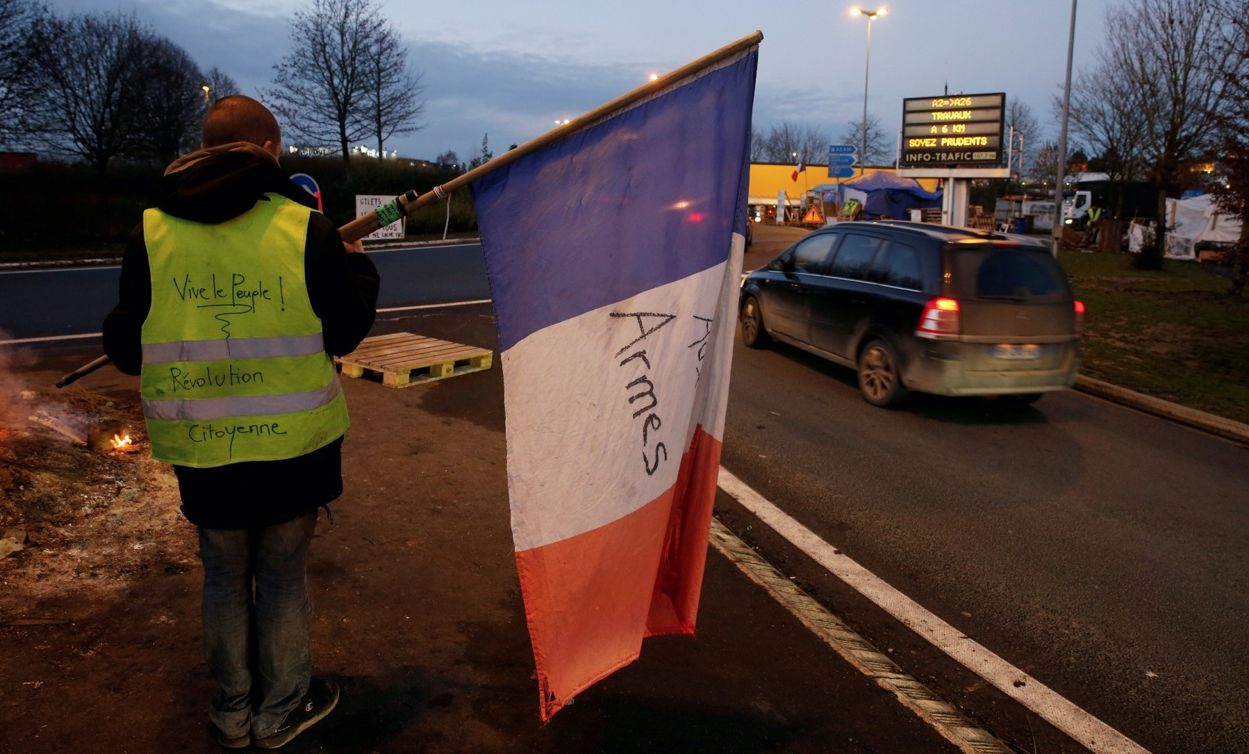 A protester, wearing a yellow vest, holds a French flag, in Fontaine-Notre-Dame, Dec. 4.