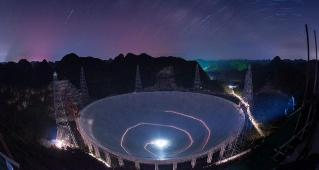 In this photo released by China's Xinhua News Agency, a vehicle leaves light trails in a long exposure photo as it drives near the 500-meter-wide Aperture Spherical Telescope FAST in Pingtang County in southwestern China's Guizhou Province, June 27, 2016. AP Photo