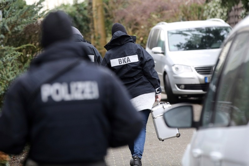 Police officer walk between cars during a raid in the village Meldorf, Germany, Jan. 30, 2019. (Bodo Marks/dpa via AP)