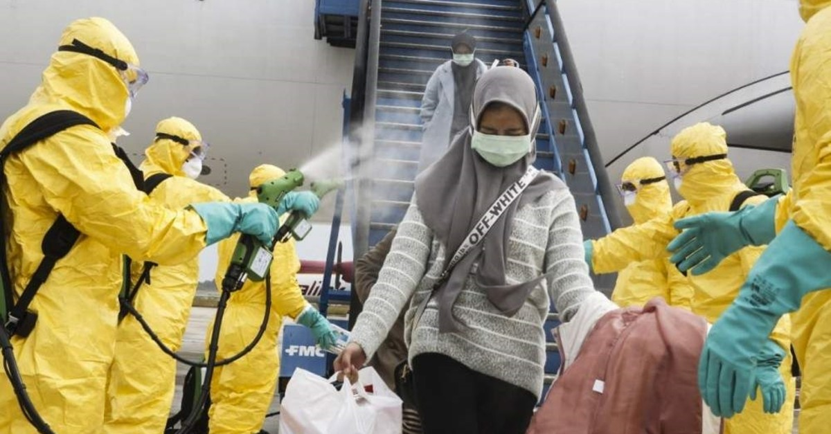 A handout photo made available by the Indonesian Foreign Ministry shows Indonesian nationals, who were evacuated from Wuhan, China, being sprayed with antiseptic as they arrive at Hang Nadim Airport in Batam, Indonesia, Feb. 2, 2020. (EPA/Indonesian Foreign Ministry/Handout)