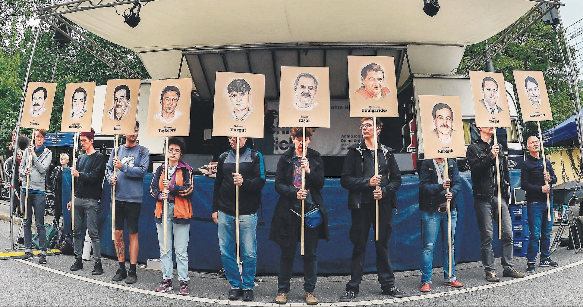 People hold portraits of NSU victims in front of the Higher Regional Court in Munich, July 10, 2018.