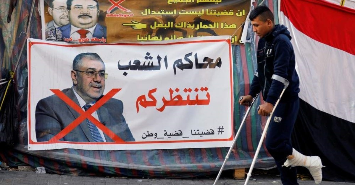 An Iraqi demonstrator on crutches walks next to a poster depicting the outgoing Higher Education Minister Qusay al-Suhail, a nominee for the prime minister office, Baghdad, Dec. 23, 2019. (REUTERS Photo)