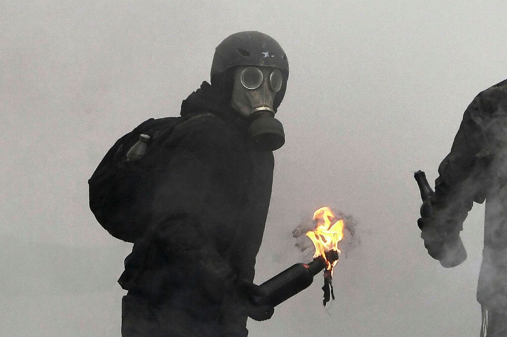 An anarchist protester throws a Molotov cocktail as clashes erupt during the Gendarmerie operation to raze the squat camp at Notre-Dame-des-Landes, April 10.