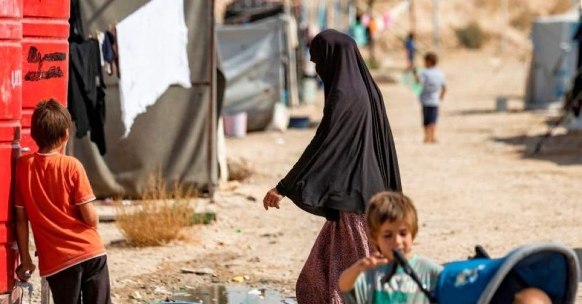 A woman and child are seen near a water tank at the al-Hol camp for the displaced where families of Daesh members are held, in the al-Hasakeh governorate in northeastern Syria. (AFP Photo)