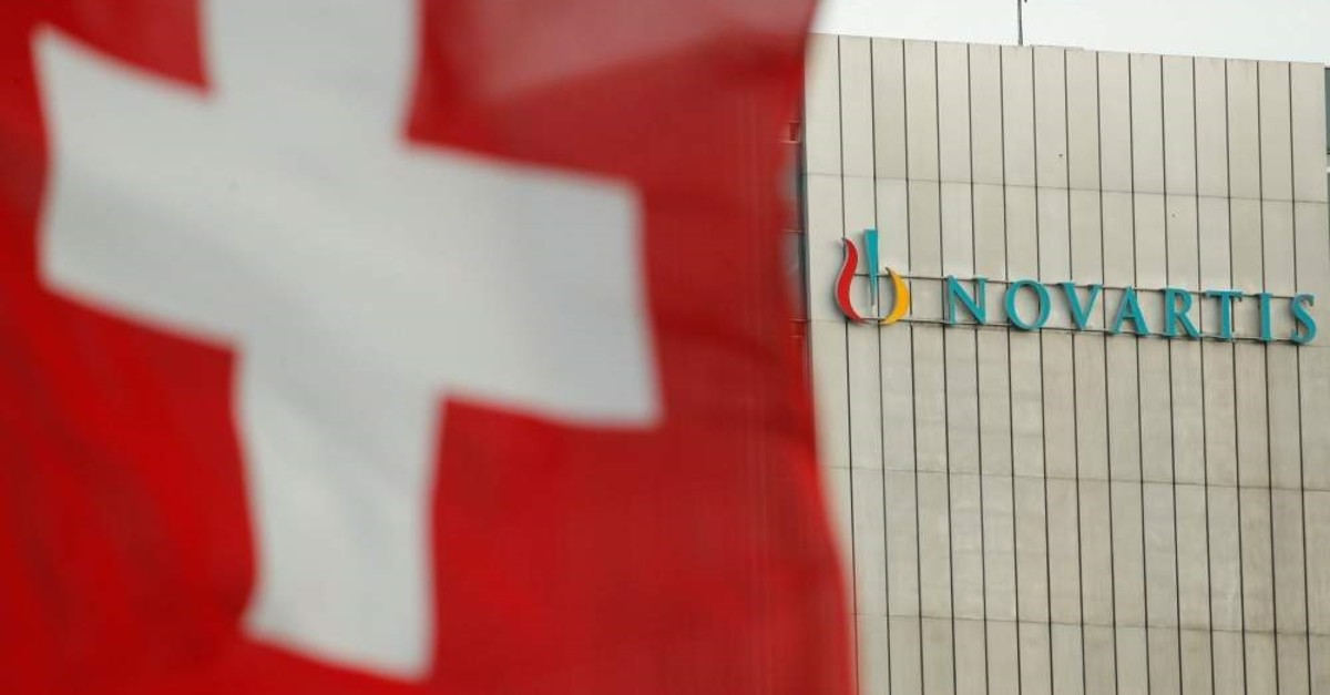 Switzerland's national flag flies in front of the logo of Swiss drugmaker Novartis in Basel, Switzerland, Jan. 30, 2019. (Reuters Photo)