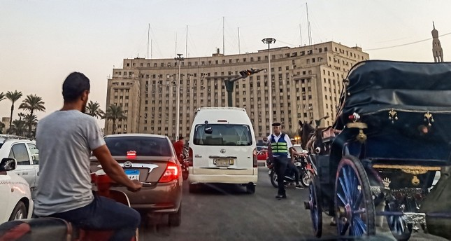 A policeman stops traffic traversing the roundabout in the Egyptian capital Cairo's central Tahrir Square on September 21, 2019 (AFP Photo)