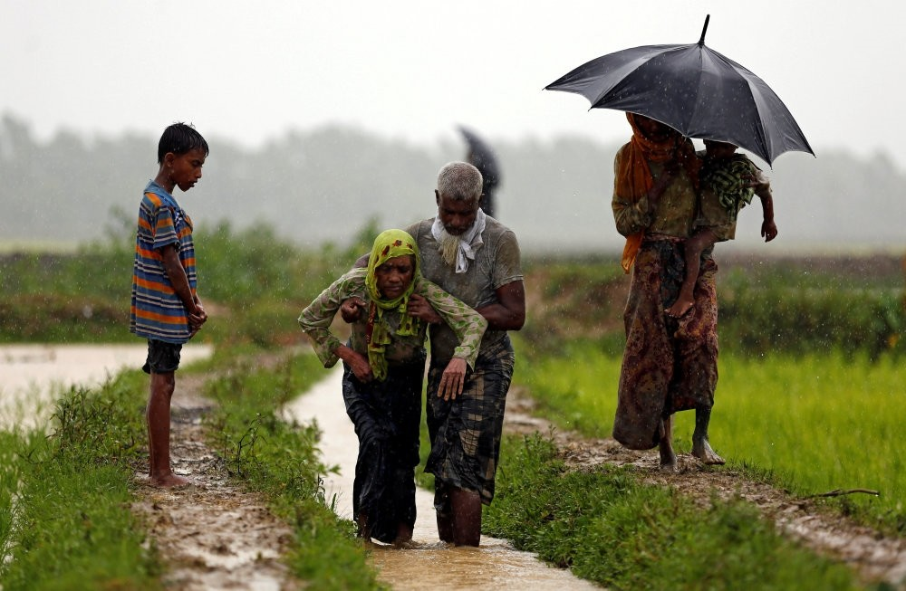 A Rohingya refugee man helps a woman to walk after crossing the border, Teknaf, Bangladesh Sept. 1.