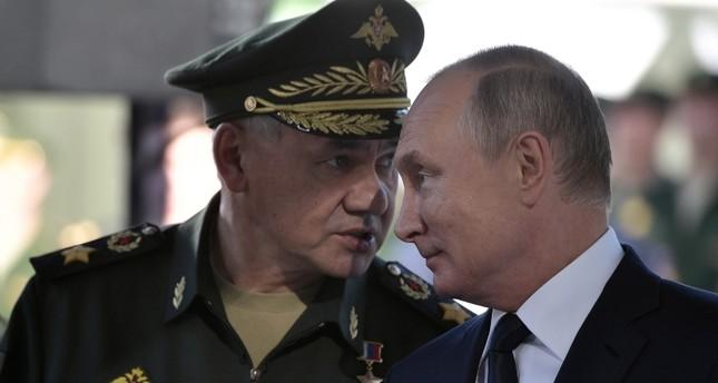 الرئيس الروسي منصتاً إلى وزير دفاعه أمس (رويترز)
