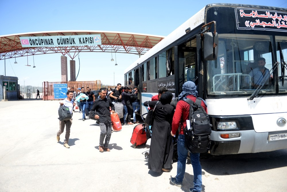 Syrians board buses that will take them to inner towns of their country after crossing the u00d6ncu00fcpu0131nar border crossing.