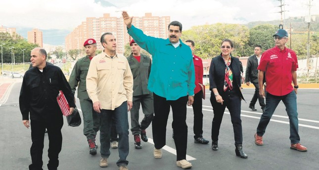 Venezuelan President Nicolas Maduro (C) waves during a government event in Caracas.
