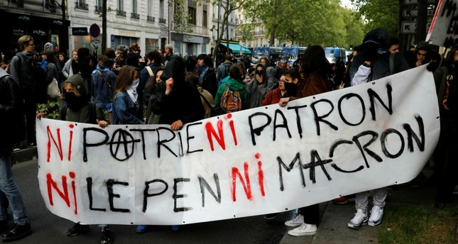 Students hold a banner reading No Nation, No Boss, No Le Pen, No Macron as they clash with riot police in an improvised march near Place de la Bastille, in Paris, France, April 27.