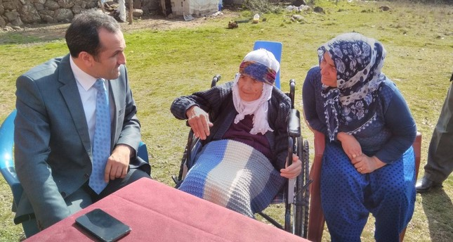 The provincial director of Family and Social Policy Ministry, Ali Sandıkçı (L), and Azime Hussain (C), with a relative.
