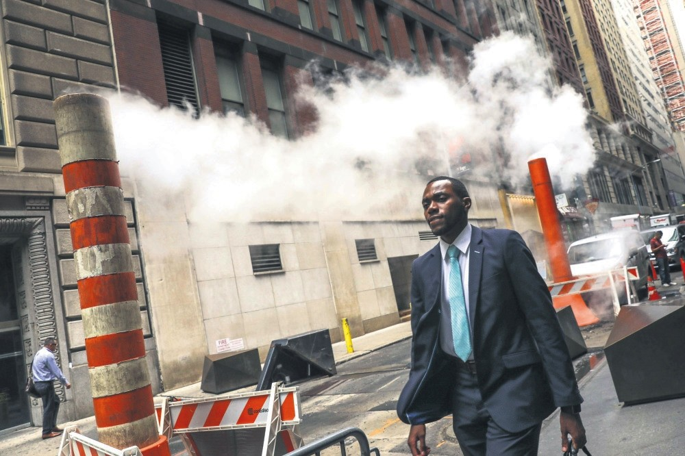 A suited businessman walks through the financial district near Wall Street in New York City, Aug. 22.