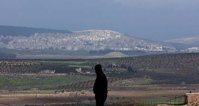 A civilian fleeing the city of Afrin (background) in northern Syria stands at the mountainous road of al-Ahlam as he heads towards the check point in az-Ziyarah, in the regime-controlled part of the Aleppo province, on March 15, 2018. (AFP Photo)