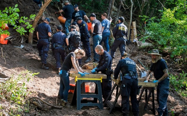 In this July 5, 2018, file photo, members of the Toronto Police Service excavate the back of a property in Toronto during an investigation in relation to alleged serial killer Bruce McArthur. (Tijana Martin/The Canadian Press via AP)