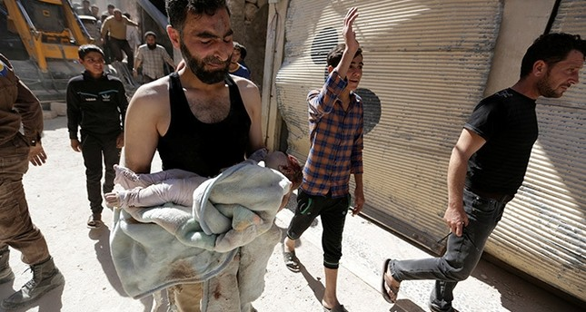 A civil defence member mourns as he carries the body of a dead child at a site hit by airstrike in the rebel-controlled area of Maaret al-Numan town in Idlib province, Syria, June 12, 2016. (Reuters Photo)