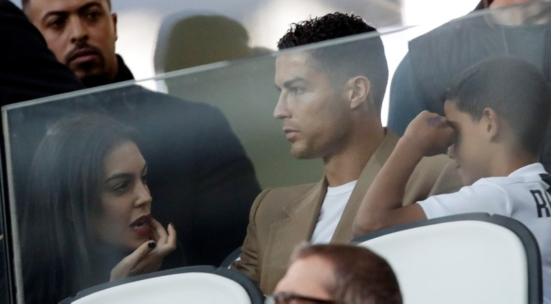 In this Oct. 2, 2018 filer, Juventus forward Cristiano Ronaldo, center, is flanked by his girlfriend and son, as he sits in the stands during a Champions League match between Juventus and Young Boys, at the Allianz stadium in Turin, Italy. (AP Photo)