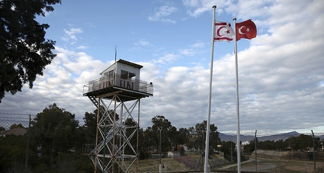 A UN guard post is seen on the buffer zone as a Turkish and a Turkish Cypriot flag wave on the Turkish Cypriot northern part of the divided city of Nicosia (AFP Photo)