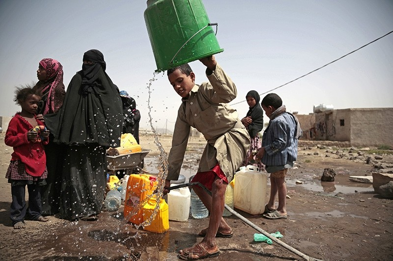 In this July 12, 2017 file photo, a boy rinses a bucket as he and others collect water from a well that is allegedly contaminated with cholera bacteria, on the outskirts of Sanaa, Yemen. (AP Photo)