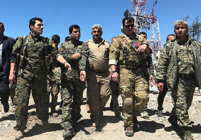A U.S. military commander (2nd R) walks with militia from the People's Protection Units (YPG) at the YPG headquarters that was hit by Turkish airstrikes in Mount Karachok near Malikiya, Syria, April 25, 2017. (Reuters Photo)