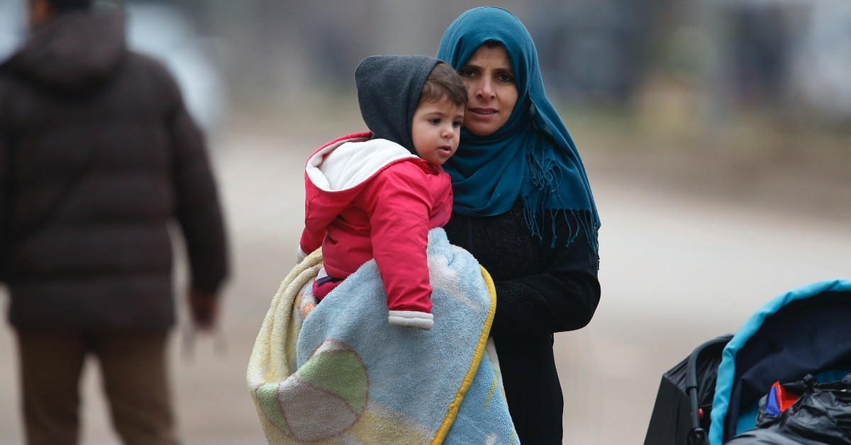 A Syrian woman holding a child walks towards Syria from Turkey at the u00d6ncu00fcpu0131nar border crossing with Syria, Kilis, Turkey, Jan. 26. 2018.
