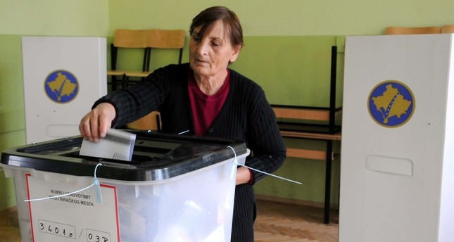 A woman casts her vote into a ballot box at a polling station in Gracanica, near Pristina, Kosovo, Oct. 6, 2019. (Reuters Photo)