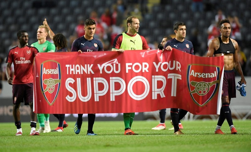 Arsenal players hold up a banner in front of the fans on August 4, 2018. (Reuters Photo)