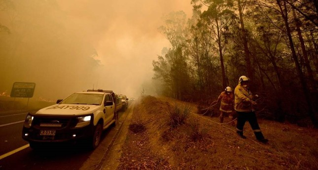 Firefighters tackle a bushfire amid thick smoke in the town of Moruya, south of Batemans Bay, in New South Wales, Jan. 4, 2020. AFP Photo