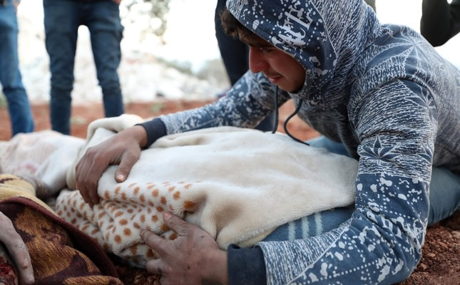 A young Syrian man mourns over the blanket-clad body of a child, killed along with six other members of a family, in a house hit in a reported airstrike by pro-regime forces in the town of Sarmin in the northern Syrian Idlib province on Feb. 2 AFP