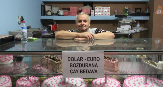 Baker Burhan Uğurlu from Düzce is offering customers free tea if they sell their dollars or euros while Hasan İzol from Gaziantep (below) is burning single dollar bills in protest.