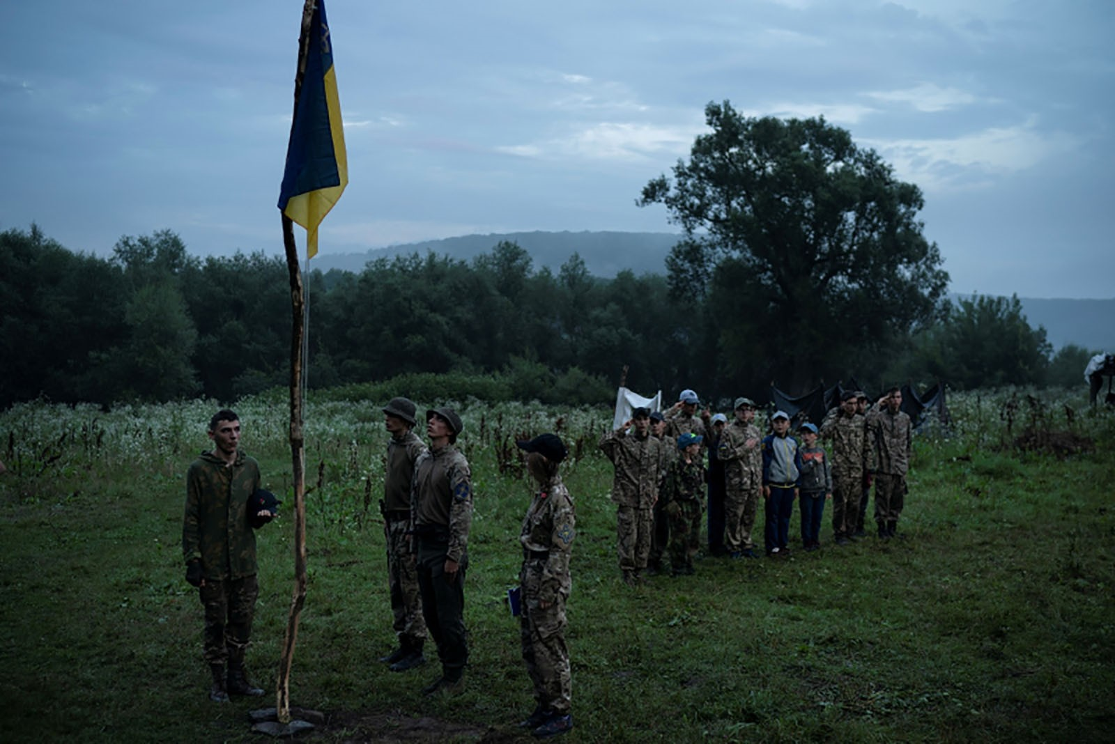 Young participants and instructors of the camp stand in formation as they sing the national anthem.