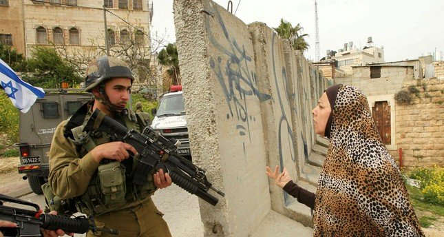 A Palestinian woman speaks with an Israeli soldier at the entrance of the heavily guarded Jewish settler enclave in the city center of the West Bank on March 24.