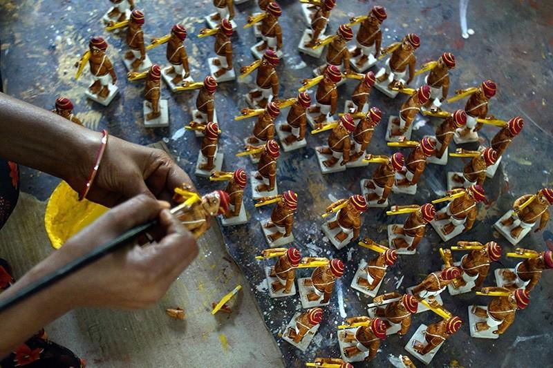 In this file photo taken on December 18, 2008, an Indian artisan applies vegetable paint to toys at a workshop in Kondapalli village in Vijayawada district of Andhra Pradesh state. (AFP Photo)