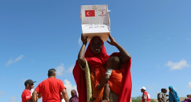 A Somali woman carries a box of food distributed by the Turkish Red Crescent in a camp, Mogadishu, Somalia, May 23, 2017.