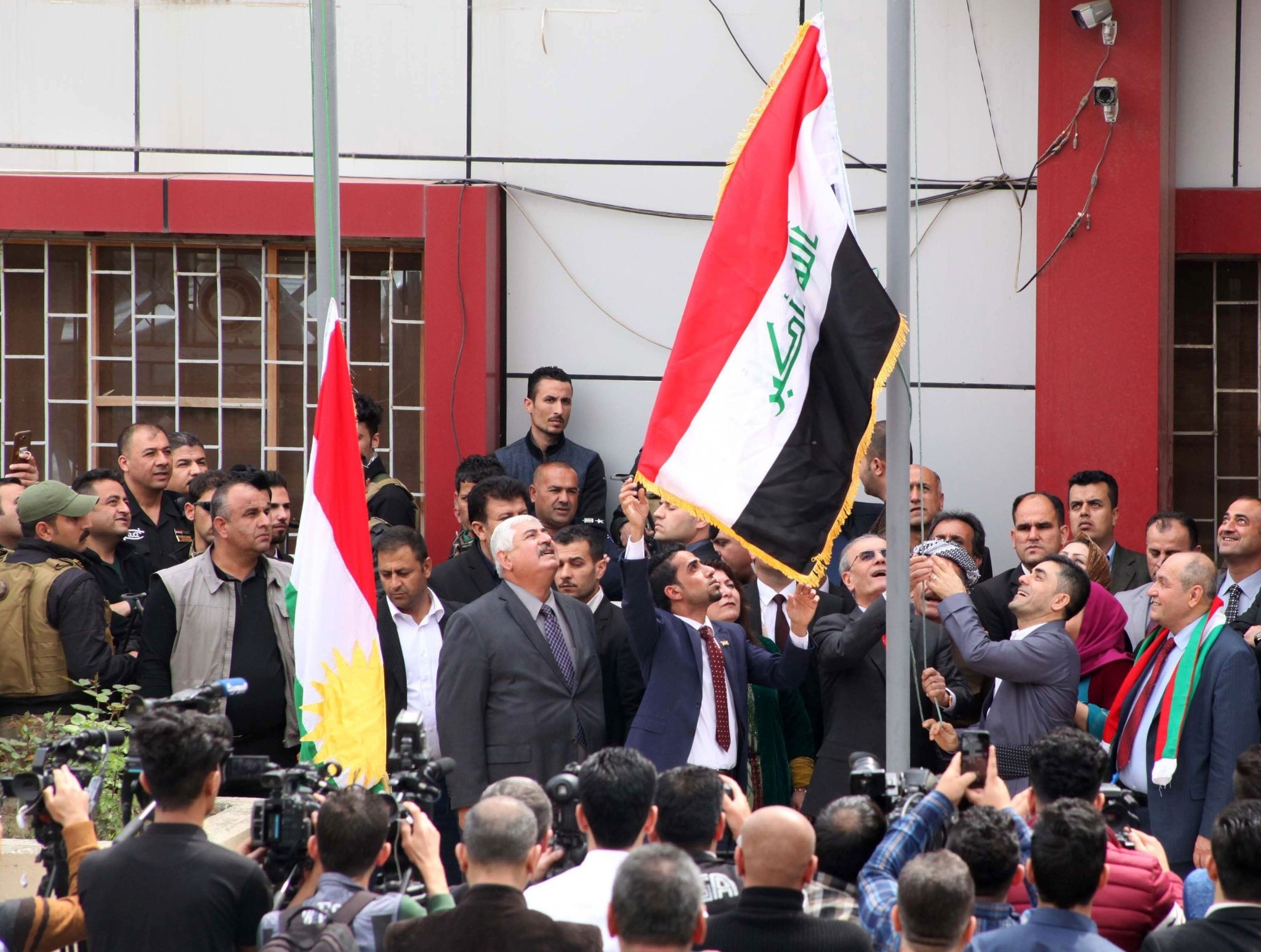 Kirkuk provincial Governor Najim al-Din Karim (C-R) raises the Iraqi flag to fly next to the Kurdish flag over a government building in the northern Iraqi city of Kirkuk on March 28. (AFP Photo)